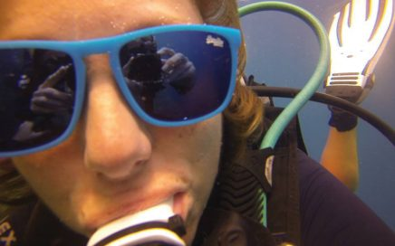 Close up of Nic wearing sunglasses underwater